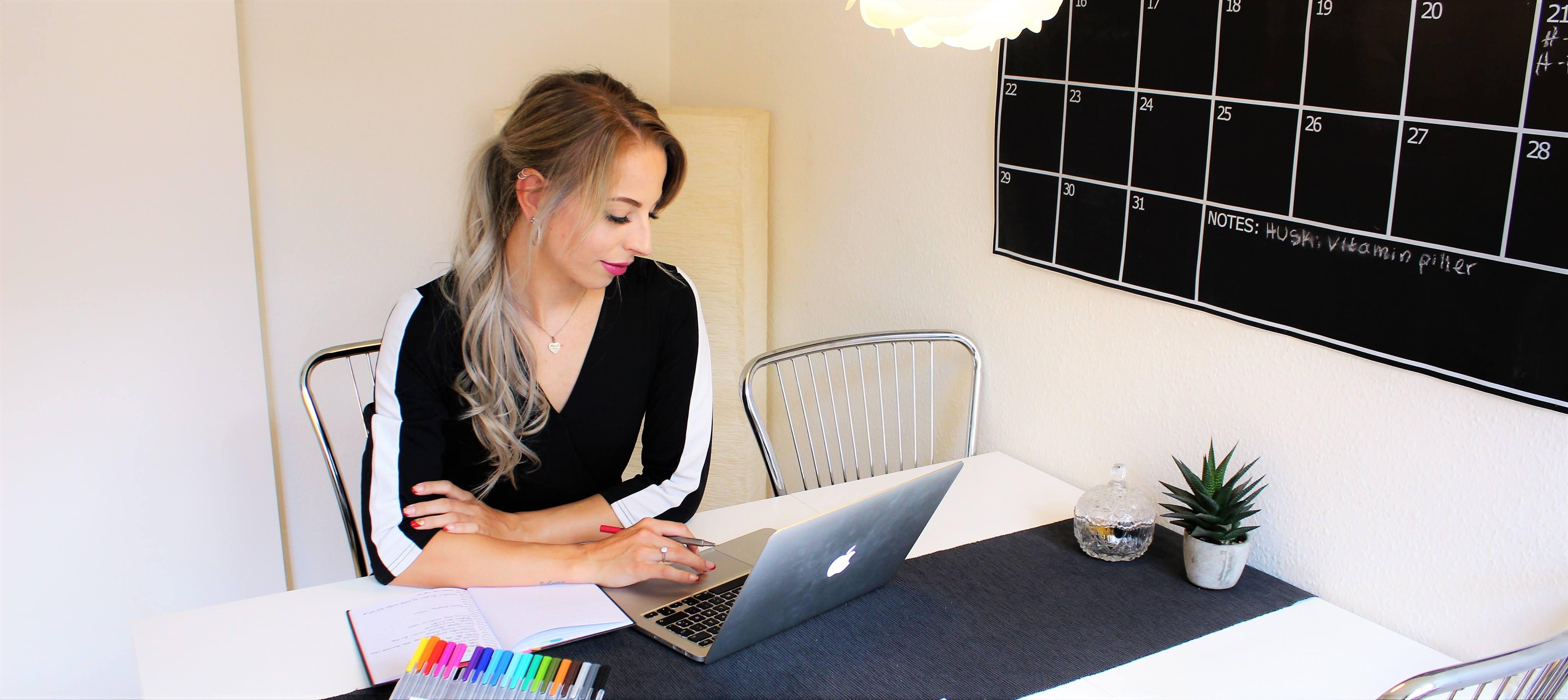 Henriette sidder med sin computer ved et bord.